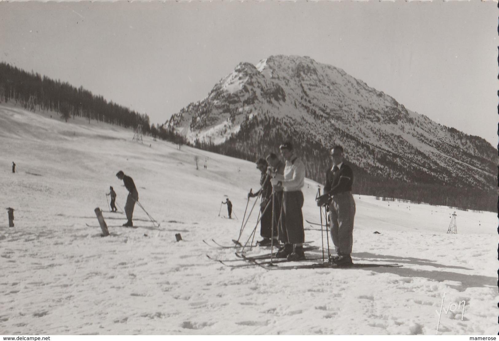 MONTGENEVRE (05). Skieurs (à L'arrêt) Sur Les Champs De Neige, Au Fond Le Mont Janus. (Carte Yvon) - Winter Sports