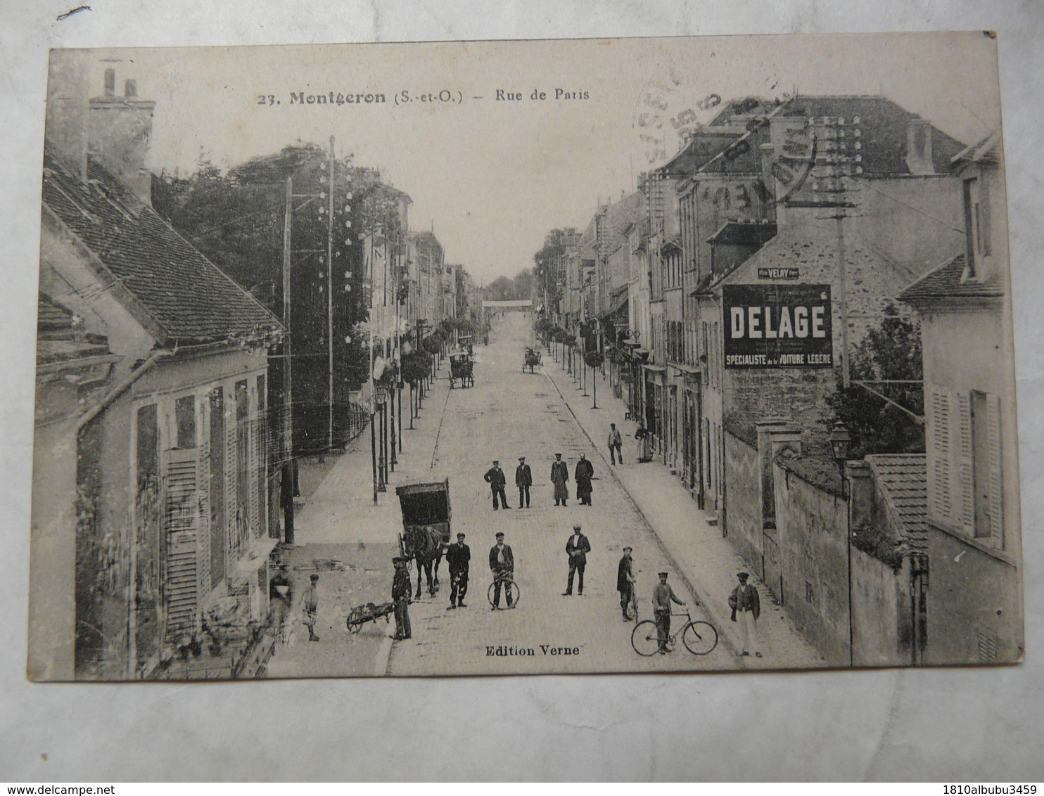 CPA 91 ESSONNE-MONTGERON : Scène Animée Dans La  Rue De Paris (un Cycliste, Des Charrettes, Une Publicité DELAGE - Montgeron