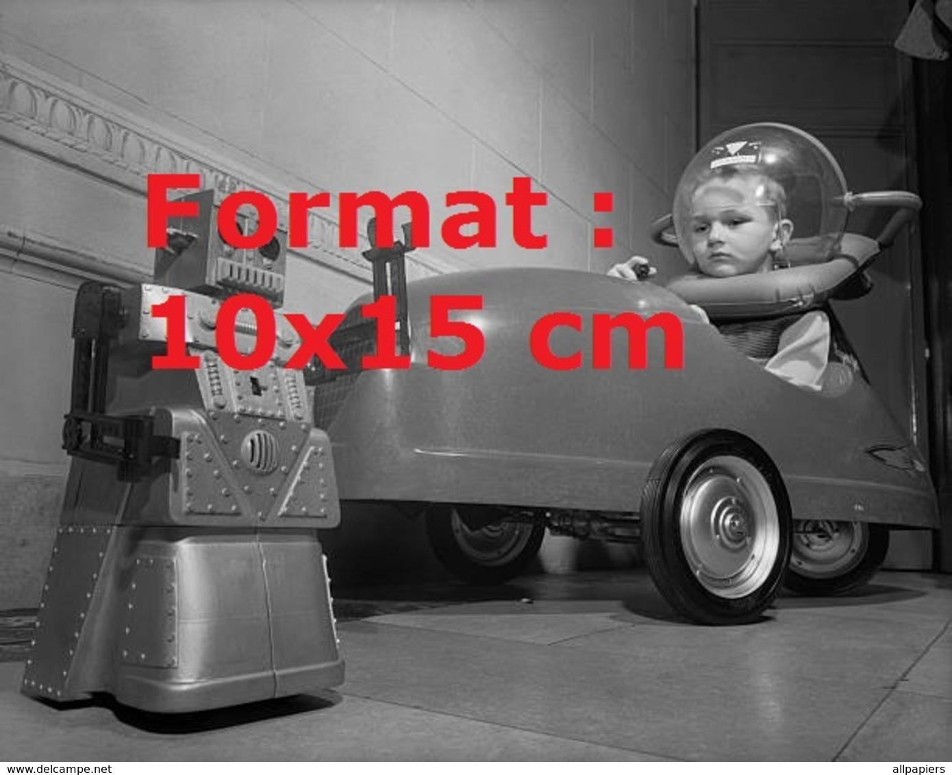 Reproduction D'une Photographie Ancienne D'un Enfant Dans Un Vaisseau Spatial à Roues Devant Un Roboten 1954 - Reproductions