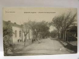 CPA Algérie  -  BOGHARI - L'école Et La Rue Principale - Autres Villes