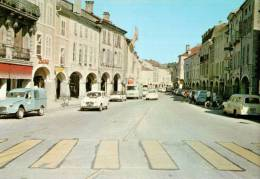 CPM REMIREMONT  Un Coin De La Ville  Avec La Grande Rue  Et Ses Commerces - Remiremont