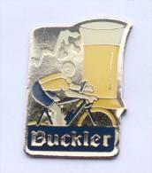Pin's Biére BUCKLER - Le Verre De Bière - Le Coureur Cycliste - Ralf - D412 - Beer