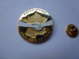 Superbe pin�s en zamac , Association main dans la main , carte de France , humanitaire