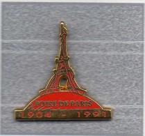 Pin´s  Ville, Foire  De  PARIS  1904 - 1991  Avec  La  Tour  Eiffel  Cartouche  Rouge  Signé  Decat - Villes