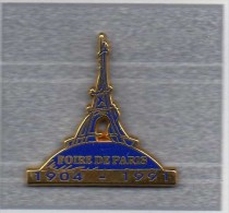 Pin´s  Ville, Foire  De  PARIS  1904 - 1991  Avec  La  Tour  Eiffel  Cartouche  Bleu  Signé  Decat - Villes
