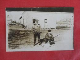 RPPC   Two men with shotguns & Dog  has crease - ref 1774