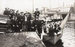 Carte Photo - Groupe De Personnessur Barque Et Quai , Portant Un Chapeau Avec Initiales :A . L - A Identifier
