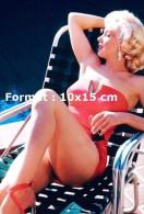 Reproduction D'une Photographie De La Belle Marilyn Monroe En Maillot De Bain Rouge Sur Une Chaise Longue - Reproductions