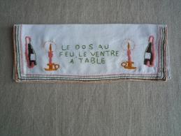 Porte-serviette en lin brod� par A. Soubrane vin et bougeoir Le dos au feu, le ventre � table . Voir photos