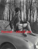 Reproduction D'uPhotographie D'une Jeune Femme Assise Sur Le Capot D'une Automobile Montrant Ses Bas Et Porte-jarretelle - Reproductions