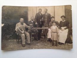 Carte photo. 4 hommes, 2 femmes et 1 enfant endimanch�s autour d'une table. Seuls les hommes boivent !!