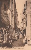 Le Mont  St Michel - La Rue - Marchand De Cartes Postales - Scan Recto-verso - Le Mont Saint Michel