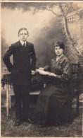 Carte Photo Originale Couple - Beaux Jeunes Gens En Studio, Femme à La Lecture Sur Fauteuil - Personnes Anonymes
