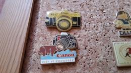2  Pins Sur La Photo Appareil Photo Canon Dont Un Arthus Bertrand - Pin's & Anstecknadeln