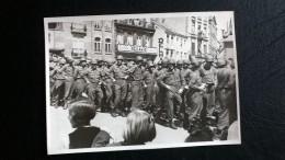 """Une Photo De Militaires , En File, En Ville, Enseigne """" Ro?lants"""". Cachet Au Dos: Un Nom( De Militaire?) , Ville Heusy. - Guerra, Militari"""