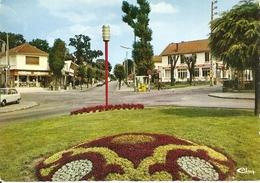 91. CPM. Essonne. Sainte-Geneviève Des Bois. Place De La Gare (animée, Autos, R6, Librairie Papeterie, Relais Hôtel, Etc - Sainte Genevieve Des Bois