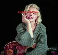 Photographie D'un Portrait De Marilyn Monroe En Gros Pull Appuyée Sur Une Guitare Et Tenant Une Cigarette - Reproductions