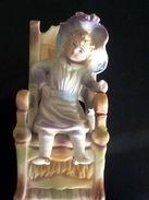 Statue En Porcelaine Biscuit Polychrome Représentant Une Jeune Fille Assise Sur Une Chaise - Céramiques