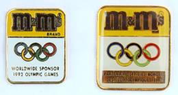 Lot De 2 Pin's M&M'S - Sponsor Officiel Des J.O 1992 - Anneaux Olympiques  - G968 - Badges