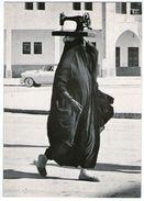 CPM    PHOTOGRAPHE JEAN PHILIPPE CHARBONNIER    KOWEIT      FEMME VOILEE QUI PORTE SA MACHINE A COUDRE SUR SA TETE 1955 - Kuwait