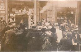 Carte-photo Scène De Rue, Attroupement Dans Une Rue Commerçante, Autour D'hommes Masqués , L'un Réalisant Une Cuisson - Anonymous Persons
