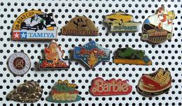 Lot De 12 Pin's Jouets Dont 1 émaillé TAMIYA 1 Doré MONOPOLY 3 BARBIE 2 MAJORETTES 1 SOLIDO 1 DINKY - Autres