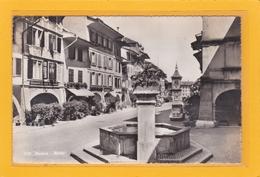 SUISSE - FRIBOURG - MURTEN-MORAT - Vue Sur Une Rue Et La Fontaine ( 4 Chevaux Renault ) + Commerces Librairie - FR Fribourg