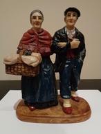 Pareja De Abuelos Tradicionales Sosteniendo Un Cesto Y Fumando Con Pipa. - Sculptures