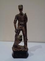Trofeo De Pesca. Escultura De Un Pescador De Pie Sacando Un Pez Con La Sacadera. - Esculturas