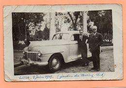 CARTE PHOTO DE 1949 - PEROU - LIMA - DEUX HOMMES DEVANT LEUR VOITURE AMERICAINE AU JARDIN DU TOURING CLUB - Pérou