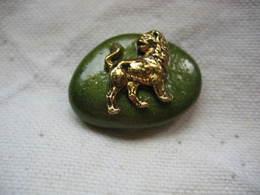 Pin's D'un Lion Doré Collé Sur Un Petit Galet Peint En Vert. Pin's Fabrication Artisanale - Animali
