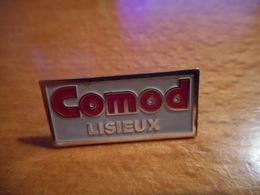 A018 -- Pin's Comod Lisieux -- Exclusif Sur Delcampe - Trademarks