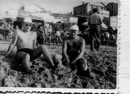 Photo De Deux Homme Torse Nue Et En Maillot De Bain Assis A La Plage - Anonymous Persons
