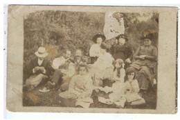 PHOTO ANCIENNE-PHOTO D'UN GROUPE DE D'HOMMES DE FEMMES ET D'ENFANTS ASSIS DANS UN PRÉ- - Personnes Anonymes