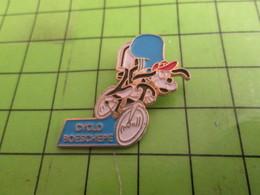 811F Pin's Pins : BEAU ET RARE /  THEME ANIMAUX : CHIEN SUR UN VELO ROUE CYCLO BOESCHERE - Animaux