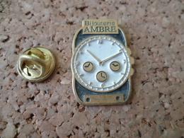 PIN'S    MONTRE   BIJOUTERIE  AMBRE - Badges