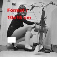 Reproduction D'une Photographie Ancienne D'un Jeune Femme En Robe Courte Et Accroupie Réparant Sa Bicyclette En 1969 - Reproductions