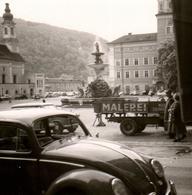 Photo Carrée Originale Volkswagen Coccinelle Ou Käfer Sur Une Place Avec Fontaine Et Camion Benne Plateau Malerei - Automobiles