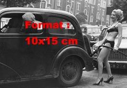 Reproduction D'une Photographie Ancienne D'une Jeune Femme En Dessous Servant Le Carburant Dans Une Station En 1965 - Reproductions