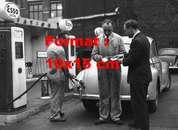 Reproduction D'une Photographie Ancienne D'un Pompiste Servant Un Homme En Carburant à Une Station Esso Extra En 1956 - Reproductions