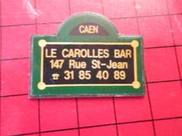 912d PIN'S PINS / Rare Et De Belle Qualité / THEME VILLES : PLAQUE DE RUE CAEN LE CAROLLES BAR RUE ST JEAN - Steden