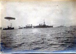 Belle Photo D'un énorme Navire De Guerre Escorté Par D'autre Navire Et Un Dirigeable - Boats
