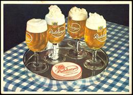"""Bier: Motivkarte """"Radeberger Pilsener"""" - Tablett Mit Vier Biergläsern Und Rot/weißen Bierdeckeln Auf Tisch Mit Blau/weiß - Ansichtskarten"""