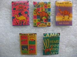 Lot De 5 Pin's Du 80eme Anniversaire Du Tabac CAMEL. Art 1, Art 2, Art 3, Art 4, Art 5. - Badges