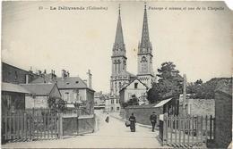 D14 - LA DELIVRANDE - PASSAGE A NIVEAU ET VUE DE LA CHAPELLE - Quelques Personnes Sur La Route - La Delivrande