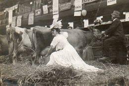 Au Salon Agricole Une Femme En Robe D'apparat Trait Une Vache - Personnes Anonymes