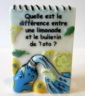 Fève Brillante Devinette  -  Quelle Est La Différence Entre Une Limonade Et Le Bulletin De Toto ? - Autres
