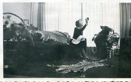 PHoto D'une Femme Et Son Chien Faisant Le Beau Dans Un Intérieur Avec Des Tapis En Peau De Félin Genre Panthère - Lugares