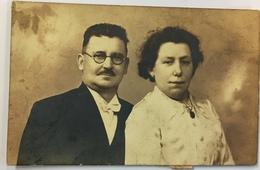 (45) Man Met Snor, Bril En Strikje En Vrouw In Een Wit Kleed En Een Kettingetje Met Medaillon - Couples