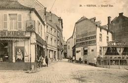Belgique. CPA. VIRTON. Grand'rue.  Commerces Delhaize, Fabrique De Hestal, Café De La Place Verte, 1919. - Virton